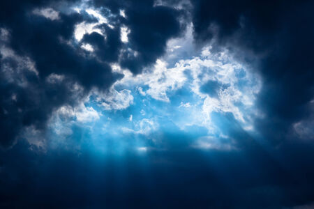 Stormy dark-blue sky with a dramatic sunbeam