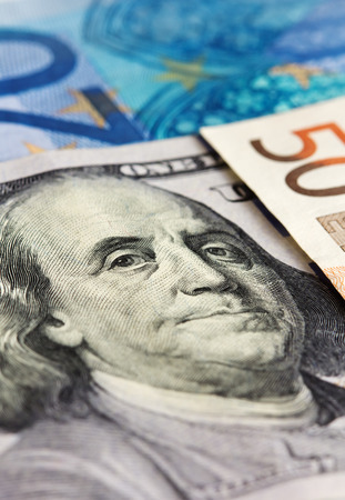 Close-up of one hundred dollar note with euro notes