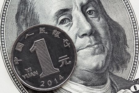 Global economics concept : chinese and american currency together. Focus on coin.
