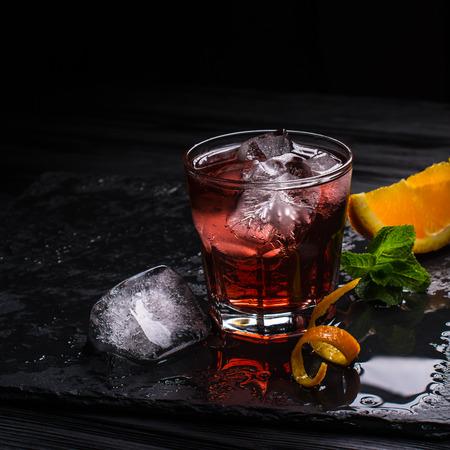 Cóctel de Mezcal Negroni. Aperitivo italiano ahumado. Piel de naranja. Foto de archivo