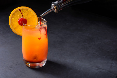 Making Tequila Sunrise Cocktail. Grenadine slowly poured into a glass of ice, orange juice and tequila. Dark stone background with copy space.