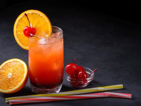 Tequila sunrise cocktail dressing orange on a dark stone background.