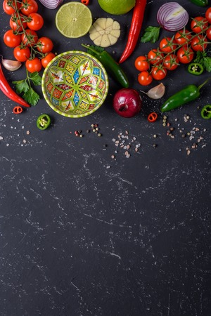 Cooking hot sauce concept. A selection of vegetables, fruits, herbs and spices for making different sauces with an empty bowl on a black stone table. Dark rusty stone table, above copy space. Фото со стока