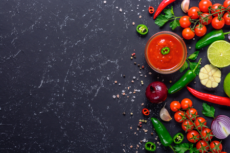 Traditional Mexican Latin American salsa sauce on black stone table. Top view copy space. Stock Photo