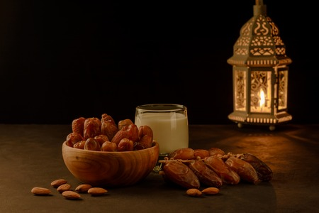 Dates in wooden bowl and lantern on stone table. Muslim holy month Ramadan Kareem.