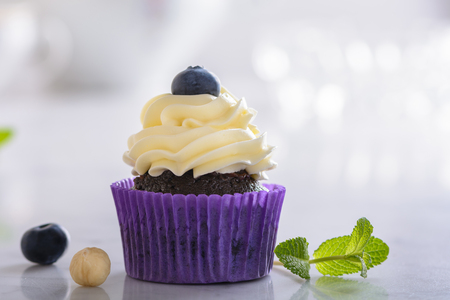 Cupcake with blueberry and hazelnut in purple paper on white natural marble surface.