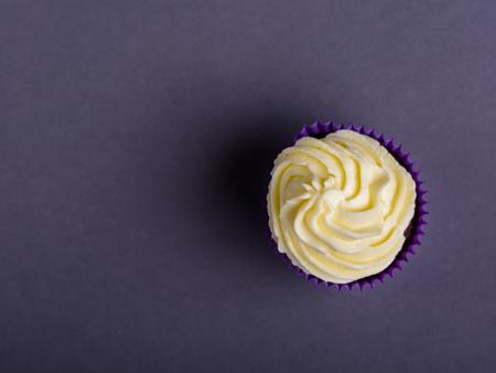 Cupcake in purple wrap on dark blue background. Minimalist. Copy space.