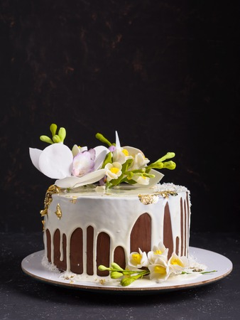 Chocolate cake decorated with flowers and poured white glaze on black stone background.