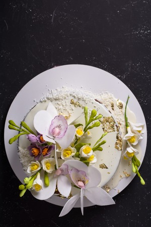 Chocolate cake decorated with flowers and poured white glaze on black stone background. Flat lay.