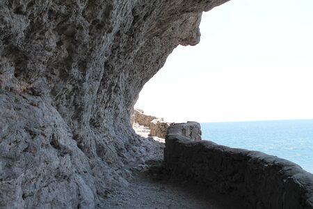 mountain trail, seashore, cliff hanging over the path, curb, blue sea, gray rocks, summer Stock Photo