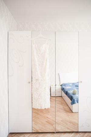 luster: wedding dress hanging on luster