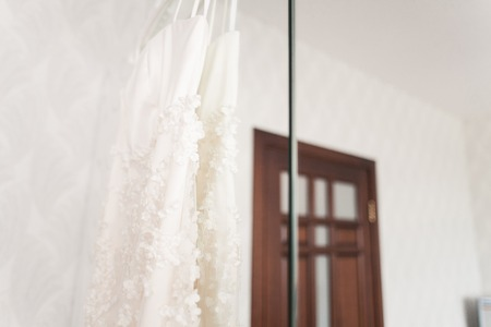 luster: wedding dress hanging on luster