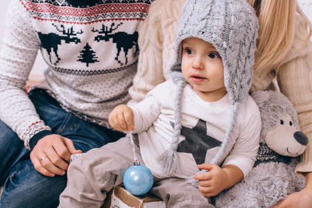 a little boy in a winter hat holding a Christmas tree ball Stok Fotoğraf