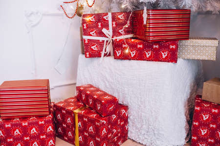 red presents lie under the Christmas tree
