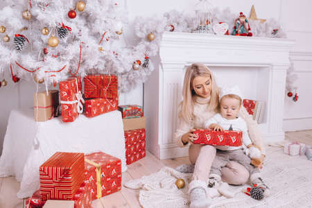A mother gives her son a gift for Christmas
