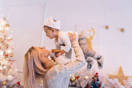 Mom plays with her son in the living room at Christmas
