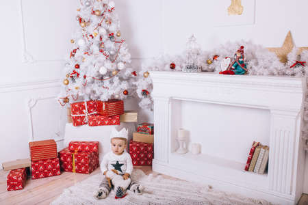 the boy sits under the Christmas tree in the room