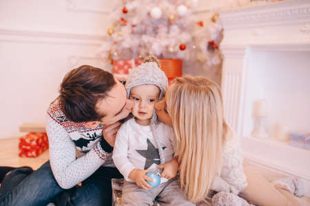 parents kissing their son on the cheeks, Christmas holiday Stok Fotoğraf