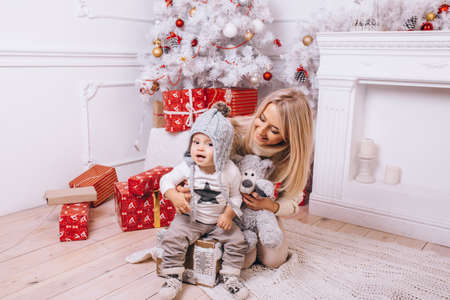 a young mother and her son celebrate christmas in a room