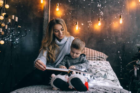 mom and little boy reading a book in the room