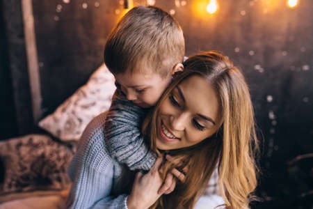 boy hugging his mother on the bed in the bedroom Stok Fotoğraf