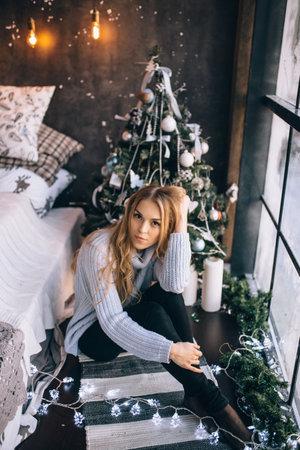 portrait of a pretty blonde girl near the window