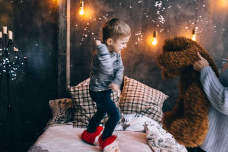 boy and mother playing with teddy bear