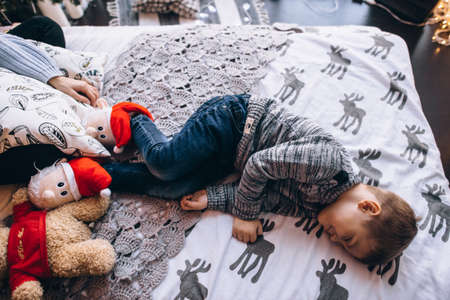boy lying on the bed with toys