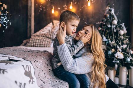 Portrait of happy mother and adorable baby celebrate Christmas. New Year's holidays. Toddler with mom in the festively decorated room with Christmas tree and decorations.