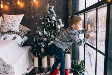 Little boy draws on a frozen window in the winter
