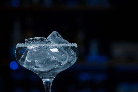 Primer plano de un chalet de vidrio lleno de hielo con un borde de azúcar está en la barra del bar con una barra borrosa en el fondo.