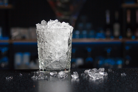 a glass filled full of crash ice, standing on the bar counter, in order to prepare and serve a chilled cocktail, blurred bar in the background. Tableware for a bar