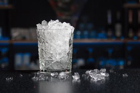 Ein mit Crash-Eis gefülltes Glas stand auf der Theke, um einen gekühlten Cocktail zuzubereiten und zu servieren. Im Hintergrund war die Bar verschwommen. Geschirr für eine Bar Standard-Bild