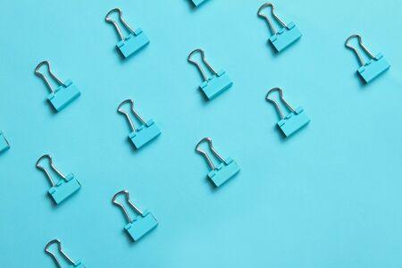 Light blue binder clips on paper background. Copy space.