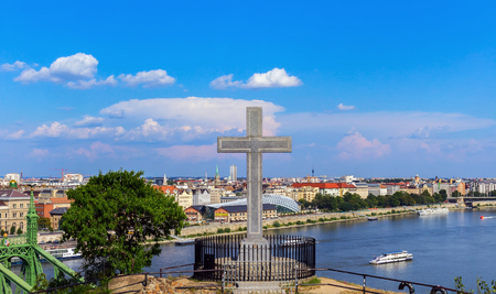 Orthodox stone cross on a high hill with a panorama of the city of Budapest