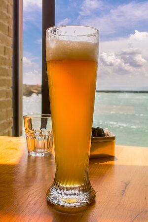 A glass of cold sweaty beer on a table in a bar overlooking the sea