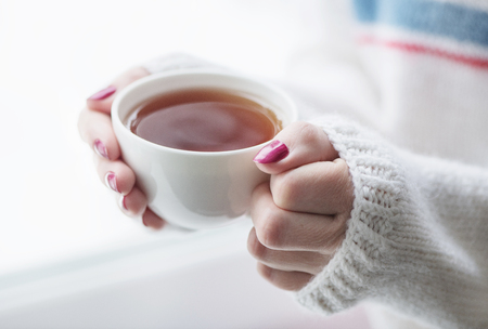 Tea drinking. The woman in a knitted, white pullover holds a cup of hot tea in her hands. Cozy weekends, winter drinks.