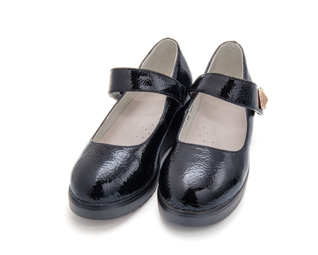 Pair of little black girls shoes isolated on the white background. Stock Photo