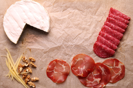 Brie cheese, salami, ham, parmesan and nuts. top view