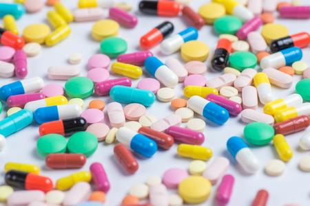 Medycyna zielone i żółte tabletki lub kapsułki na białym tle z miejsca na kopię. Zdjęcie Seryjne