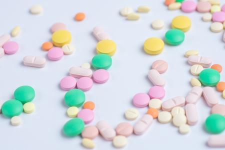 Medicina pillole o capsule verdi e gialle su sfondo bianco con spazio di copia.