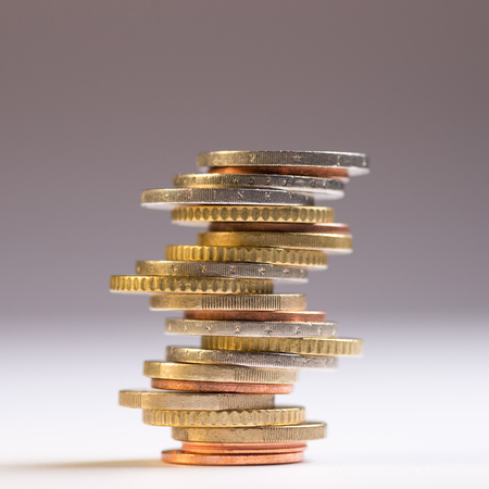 Euro coins stacked on each other in different positions. Copy space for text