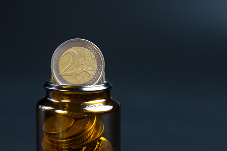 Coins in a glass bottle on a black background. Two euros.