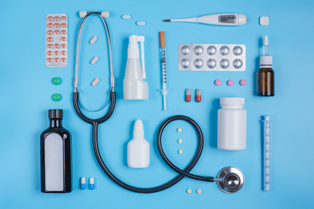 Stethoscope and pills in blisters on a blue background. Copy space for text