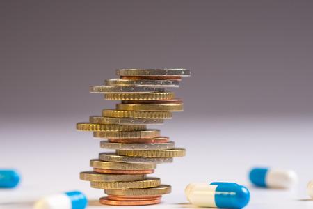 Las monedas se colocan entre sí en diferentes posiciones junto a las pastillas azul y blanca. Copiar espacio para texto