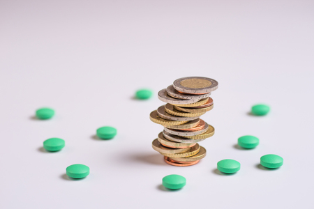Coins are placed among themselves in different positions next to the green pills. Copy space for text