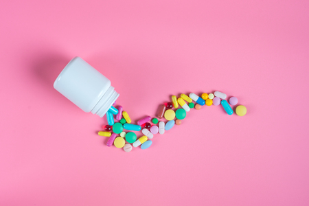 Assorted pharmaceutical medicine pills, tablets and white bottle on pink background. Copy space for text