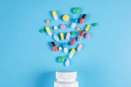 Medicine green, yellow and pink pills or capsules and white bottle on a blue background with copy space.