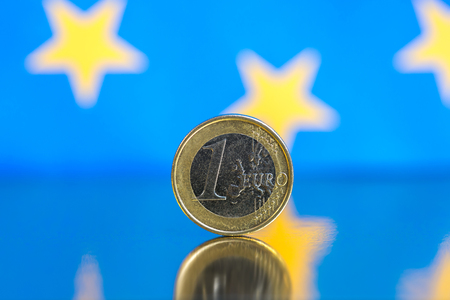 Euro coins on a blue background. Copy space for text