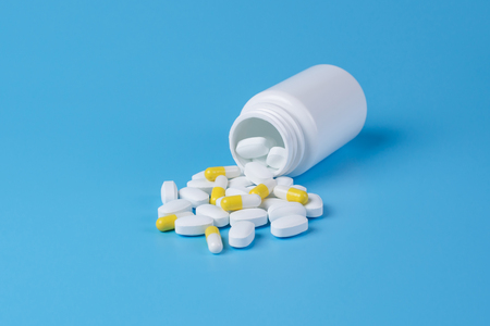 White and yellow pills, tablets and white bottle on blue background.  Copy space for text